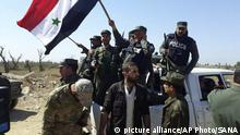 April 14, 2018*** In this photo released by the Syrian official news agency SANA, shows Syrian police units wave their national flag, as they entering the town of Douma, site of a suspected chemical weapons attack and the last rebel town in the eastern Ghouta, near Damascus, Syria, Saturday, April 14, 2018. The entry of government forces to Douma follows a Russian-mediated deal that secured the surrender and evacuation of the rebels and thousands of civilians from the town. (SANA via AP) |