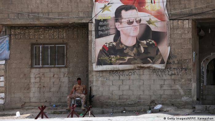 A banner of Syrian President al-Assad hangs on a wall above a soldier