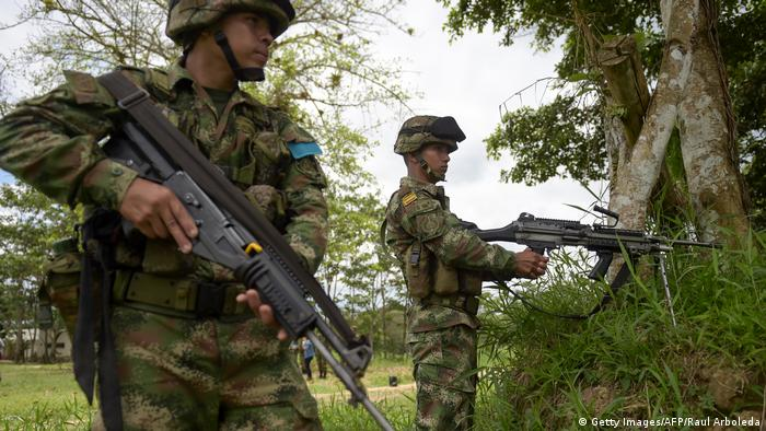 Colombian troops wait next to a tree to take part in a military operation against renegade Colombian rebels who kidnapped and killed two Ecuadorean journalists and their driver