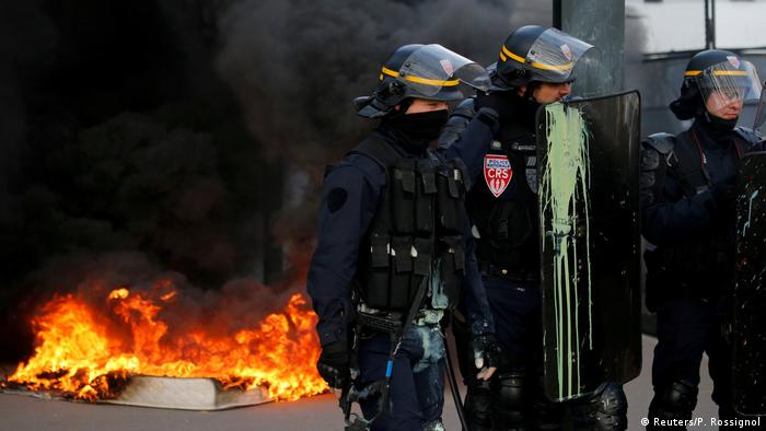 Police near flames at anti-government demonstration in Nantes, France
