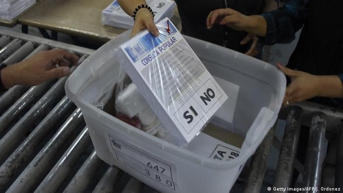 A hand places a packet of voter ballots in a bin
