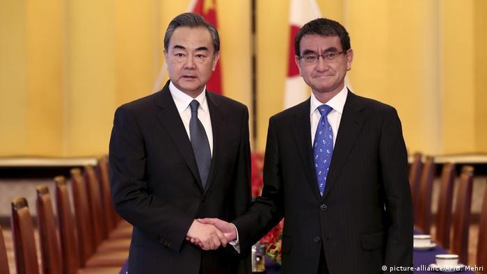 Japan, Tokio: Handschlag Außenminister Wang Yi und Taro Kono (picture-alliance/AP/B. Mehri)
