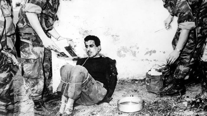 Schwarz-weiß-Foto eines Mannes während des Algerienkrieges, der mit zusammengebundenen Beinen auf dem Boden hockt. (picture-alliance/dpa/AFP)