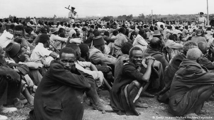 Hunderte Männer sitzen in der Hocke auf dem Boden, im Hintergrund ein Kolonialherr. (Getty Images/Hulton Archive/Keystone)