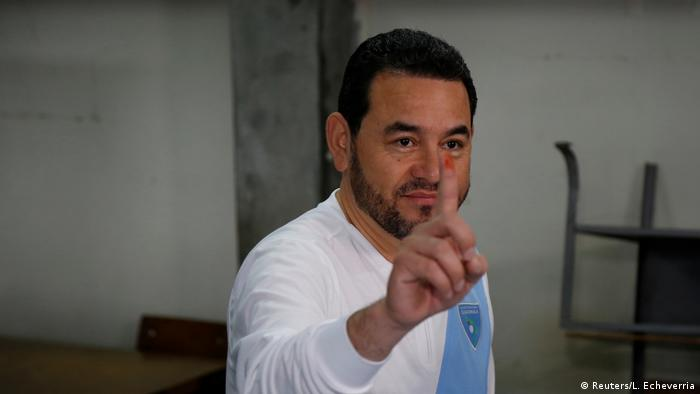 Guatemalan President Jimmy Morales holds up a ink-stained finger from voting (Reuters/L. Echeverria)