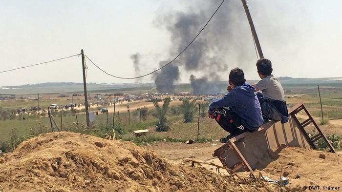Two young Palestinians look at burning tires in the Gaza Strip (DW/T. Krämer)