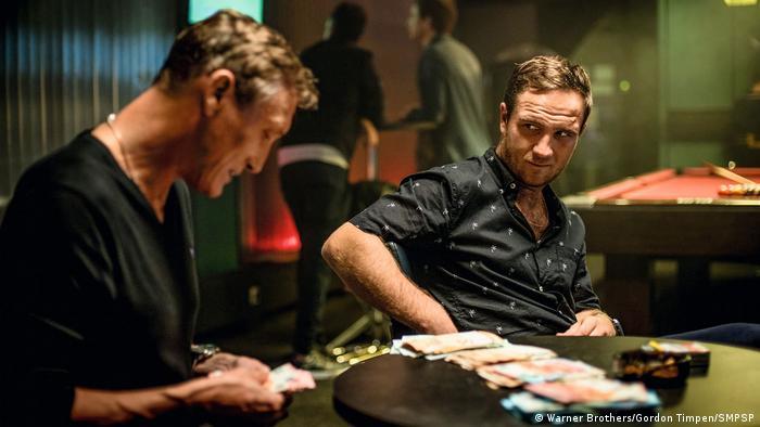 Dejan (Oliver Masucci) sitzt neben Ivo (Frederick Lau) am Tisch und zählt Geld.