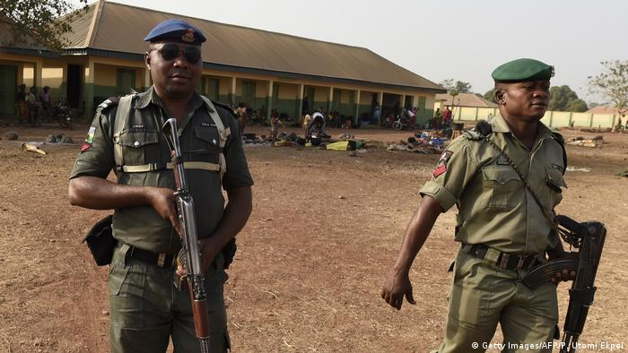 Nigerian police holding guns stand outside a building