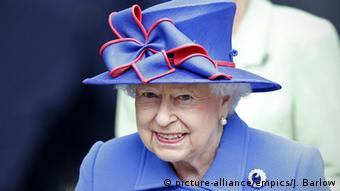 Queen Elizabeth II wears a blue outfit with red-trimmed bow on her blue hat