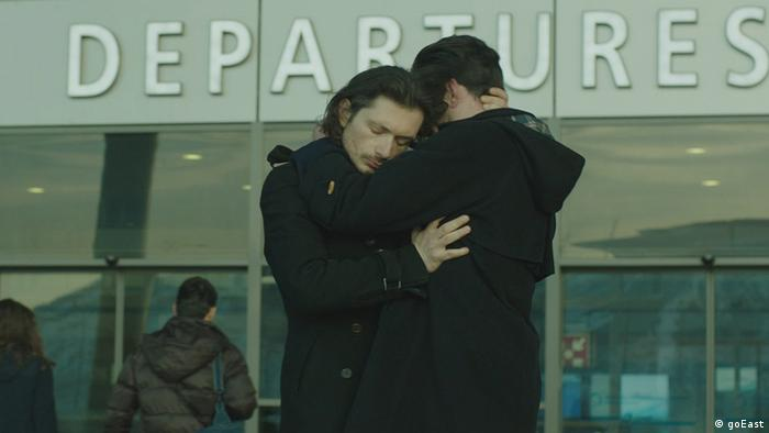 Film still shows a couple hugging in front of an airport departures terminal (goEast)