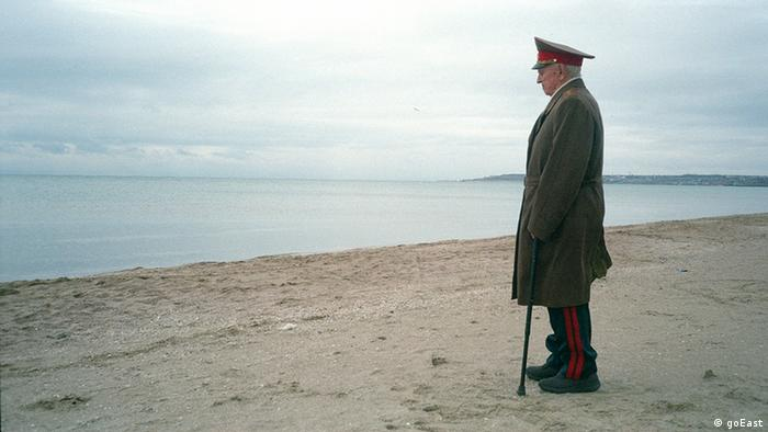 A man in soldier's uniform staring out to sea