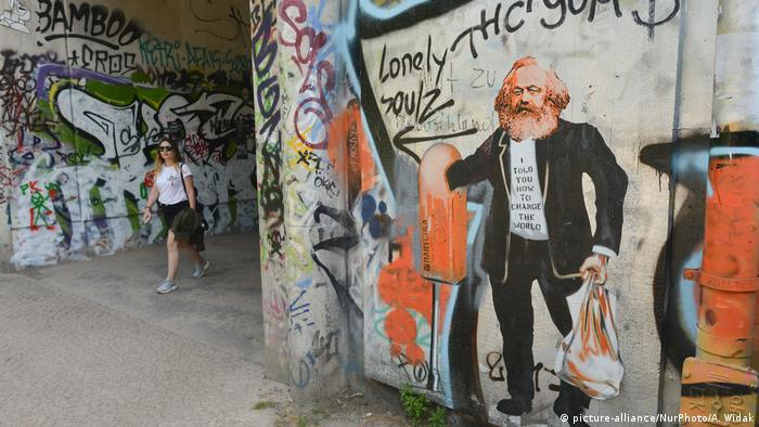 Street Art shows a picture of Karl Marx collecting empty bottles from a garbage can while wearing a shirt that reads, 'I told you how to change the world' (picture-alliance/NurPhoto/A. Widak)
