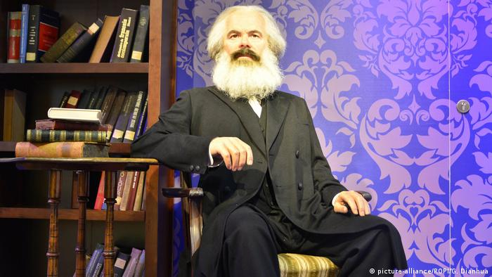A wax figure of Marx seated a table with books (picture-alliance/ROPI/G. Dianhua)