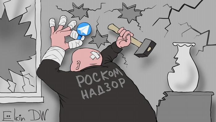 Мужчина с надписью на спине Роскомнадзор бьет молотком по значку мессенджера Telegram
