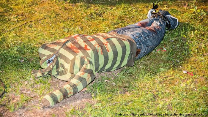 Headless figure dressed in a striped top and jeans, lying face down with bound legs in the grass (picture-alliance/dpa/Kohls/Sueddeutsche Mediengesellschaft)
