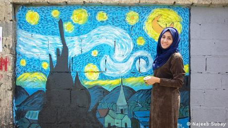 An woman standing in front of a mural in Sanaa (Najeeb Subay)