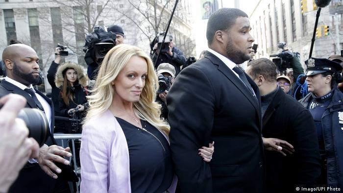 Adult-film star Stormy Daniels exits with security guards after a hearing in New York City