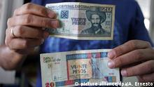 ARCHIV- A man shows two bills of 20 pesos, one of Peso Cubano 'CUP' (Top) and other of Peso Convertible Cubano 'CUC' (bottom) in Havana, Cuba, 22 October 2013. Cuban government announced the beginning of a process to eliminate the 'monetary duality' in the island to reestablish the value of the Cuban currency. EPA/ALEJANDRO ERNESTO dpa (zu dpa: Ende der Parallelwelt? Kuba will die Doppelwährung abschaffen vom 24.12.2013) +++(c) dpa - Bildfunk+++ |