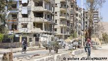 April 16, 2018*** ©Kyodo/MAXPPP - 17/04/2018 ; Men ride bicycles past ruined buildings in Douma, Eastern Ghouta, Syria, on April 16, 2018, where chemical weapons were suspected to have been used against citizens. (Kyodo) ==Kyodo Foto: MAXPPP |