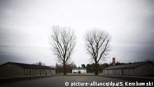 Baracken auf dem Gelände des ehemaligen KZ Sachsenhausen, im Hintergrund das Eingangstor