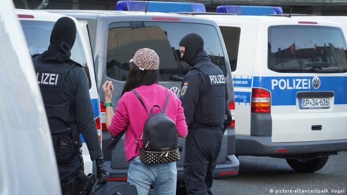 Masked police officers flank a civilian in Bonn