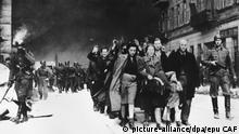 ARCHIV - Mai 1943, Polen, Warschau: Mit erhobenen Händen werden jüdische Frauen, Männer und Kinder von deutschen SS-Soldaten aus dem brennenden Ghetto der polnischen Hauptstadt Warschau getrieben. Die Aufnahme entstand in der letzten Phase des Ersten Warschauer Aufstandes, der vom 19. April 1943 bis zu seiner blutigen Niederschlagung am 16. Mai 1943 dauerte. (zu dpa «Vor dem 75. Jahrestag vom Beginns des Aufstands im Warschauer Ghetto» vom 18.04.2018) Foto: epu CAF/A0002_epu_CAF/dpa +++(c) dpa - Bildfunk+++  