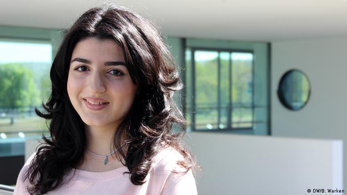 Deutschlernerin Rima (halblange dunkle, gelockte Haare, rosa Pullover und einer Kette am Hals) lächelt in die Kamera. (DW/B. Warken)
