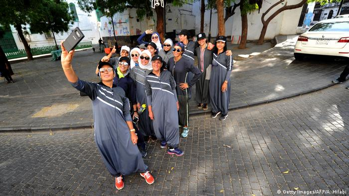 women in jogging suits take selfie (Getty Images/AFP/A. Hilabi)