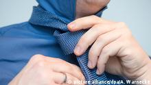 Mann bindet sich die Krawatte