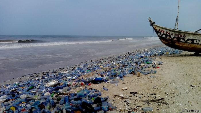 Plastic bottles washed up on the shore. A fishing boat can be seen in the background (Toa House)