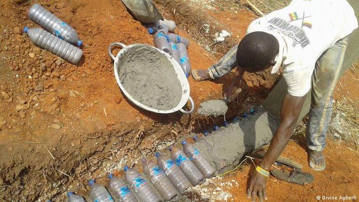 A builder applies cement to cover a row of sand-filled plastic bottles (Divine Agborli)