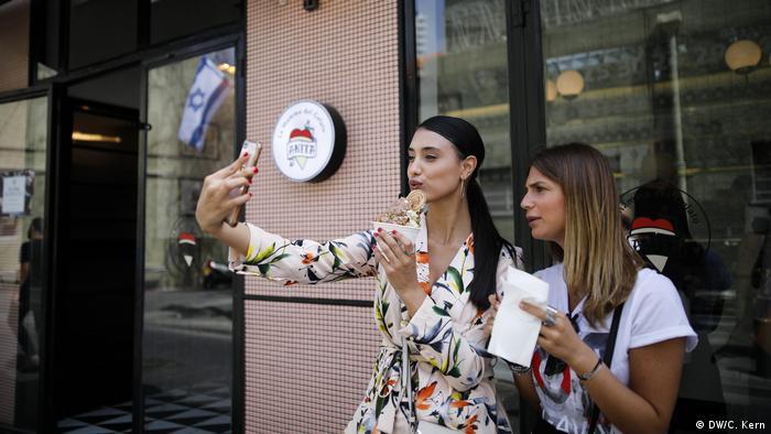Girls take selfies in Shabazi street in Neve Tzedek, Israel