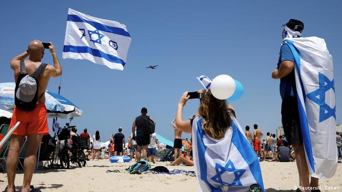 People draped in Israeli flags taking photos (Reuters/A. Cohen)