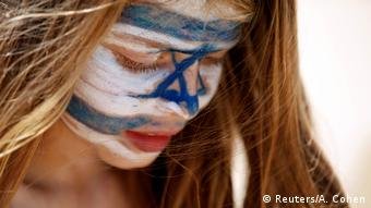 A girl with Israel's national flag painted on her face plays on the beach as part of the celebrations for Israel's Independence Day marking the 70th anniversary of the creation of the state, in Tel Aviv, Israel April 19, 2018.
