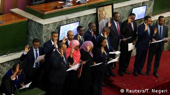 Cabinet members stand holding up their hands for the swearing in