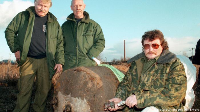 Tres especialistas en desactivación de bombas posan junto a una mina aérea.