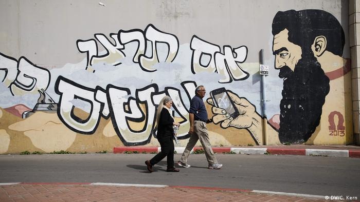 People walk past a graffiti showing Theodor Herzl, the father of modern political Zionism and referred to as the spiritual father of the Jewish State