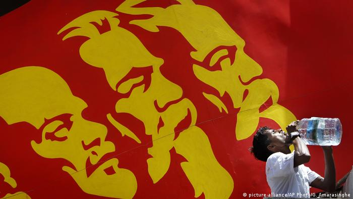 A billboard in Sri Lanka features Marx, Lenin and Engels in yellow paint on a red background (picture-alliance/AP Photo/G. Amarasinghe)