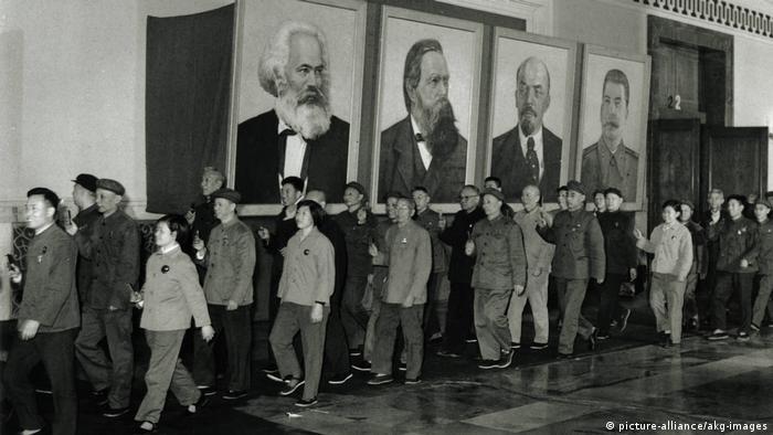 تئوری مارکس در انتقاد از کاپیتالیسم و تضاد طبقاتی بین کارگران و سرمایهداران در چین به نوع متفاوتی تعبیر شد. (عکس: رژه نمایندگان کنگره حزب کمونیست چین در آوریل سال ۱۹۶۹ از مقابل تصاویر مارکس، انگلس، لنین و استالین.)