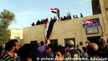 Soldiers raise the Syrian flag on a government building in the town of Dumair