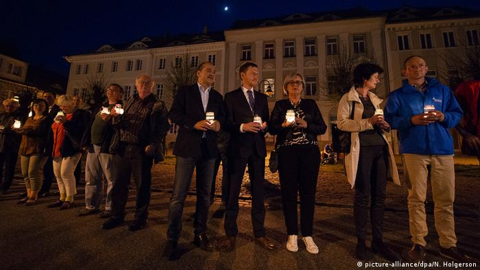 People holding candles (picture-alliance/dpa/N. Holgerson)