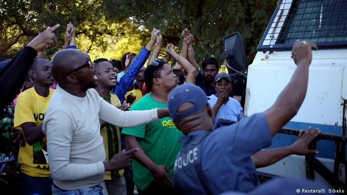 A police officer looks on as protesters chant slogans during protests in Mahikeng, in the North West province, South Africa