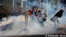 Demonstrators are seen amid tear gas during a protest over a controversial reform to the pension plans of the Nicaraguan Social Security Institute (INSS) in Managua, Nicaragua April 20, 2018. REUTERS/Oswaldo Rivas