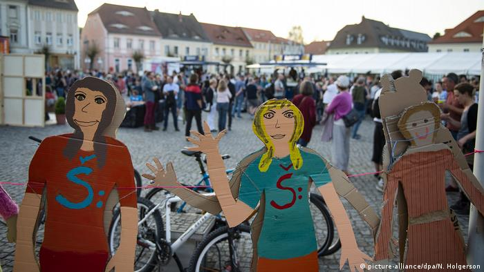 Two painted figures of women at the Peace Festival