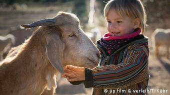 Oliver Kyr's daughter petting a goat in film still from Citizen Animal 2