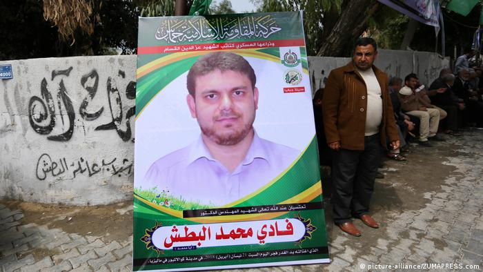 A man stands next to a large poster of slain Palestinian Fadi al-Batsh.