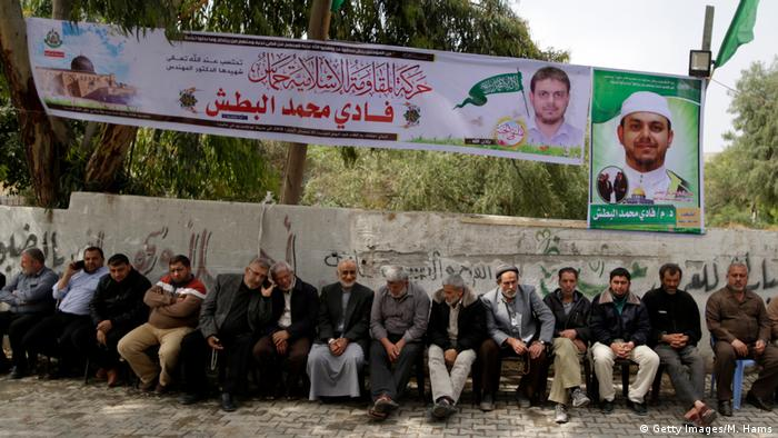 More than a dozen Palestinians sit on a bench underneath a banner, mourning the death of Fadi al-Batsh.