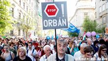 Anti-government protests in Budapest, with a man holding up a sign saying Stop Orban! (Reuters/B. Szabo)