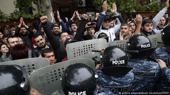 Police stand with shields in front of protesters in Armenia
