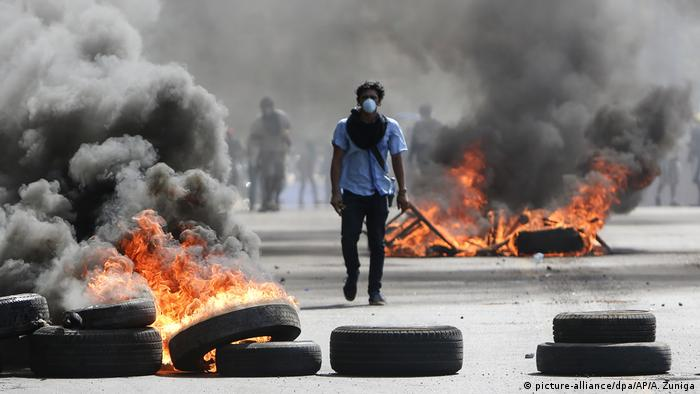 A protester surrounded by tires set ablaze